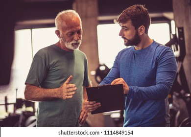 Personal trainer giving advice senior man about next exercise.