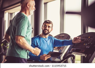 Personal trainer giving support senior man during exercise.