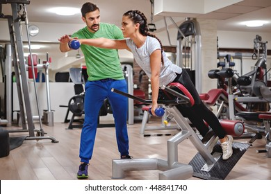 Personal trainer helping girl to train shoulders in the gym