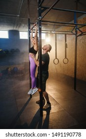 Personal trainer helping handsome sport woman doing pull up exercise in the gym with smoke and sunlight on the background .