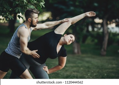 Personal trainer helping overweight woman at street workout. Fat girl doing yoga with fitness instructor. Sport, training, weight loss, teamwork and lifestyle concept.