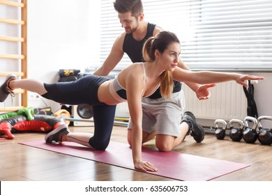 Personal trainer helping sporty woman during exercise