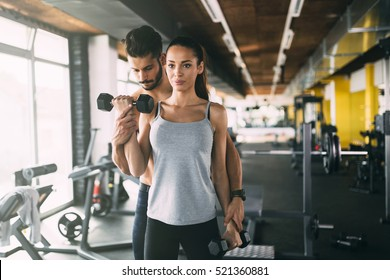 Personal trainer helping woman in gym