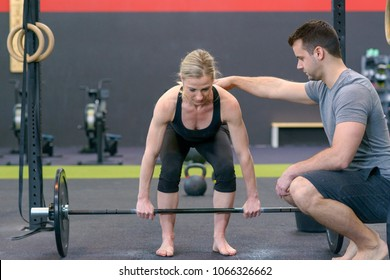 Personal trainer helping woman with lifting barbell at gym