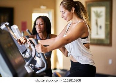 personal trainer helping woman use treadmill in gym