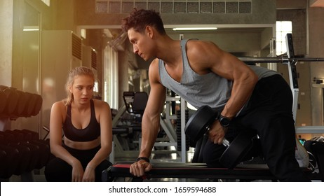 Personal trainer helping woman working with heavy dumbbells in gym