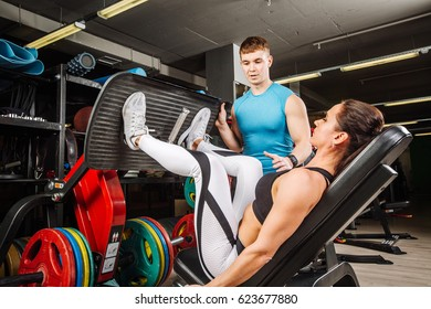 Personal trainer helping woman in works out on training apparatus inside in fitness center.  Sporty lifestyle, bodybuilding, training concept