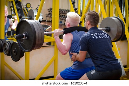 Personal trainer helping young male client in gym during workout on equipment