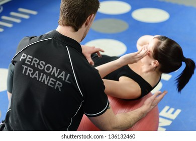 Personal trainer helping young woman in gym with crunching exercises