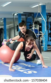 Personal trainer helping young woman in gym