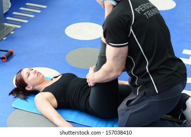 Personal trainer helping young woman in gym with stretching exercises