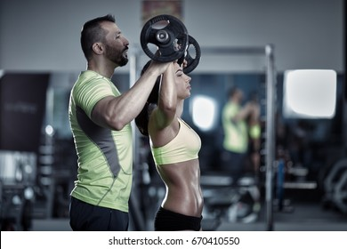 Personal trainer helping a young woman with shoulder workout