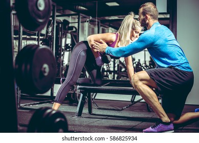 Personal trainer helps his attractive blonde female client to do one-arm dumbbell row exercise in modern gym.