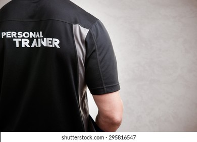 Personal Trainer, with his back facing the camera, in a grey background