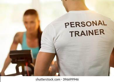 Personal trainer with his client woman on cycling machine at the gym