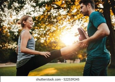 Personal trainer holding leg of woman stretching in park. Female exercising with support from her coach.