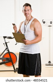 Personal trainer holding stop watch and clipboard