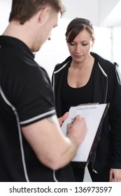 Personal trainer interviewing new client in gym