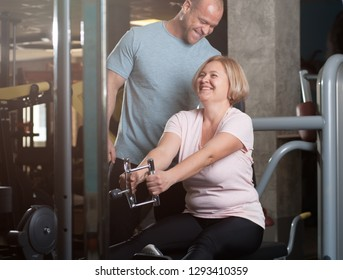 Personal trainer man helps middle aged woman to correctly perform the exercise on the simulator. The training class in the gym