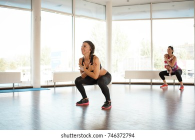 A personal trainer performs squats with a girl and a child