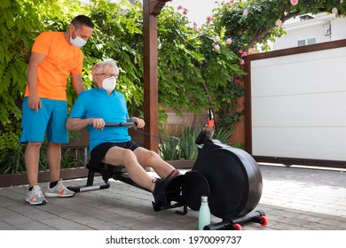 Personal trainer with protection mask and senior adult man doing rowing following the teacher's instructions. Exercises at home in times of pandemic. Home gym