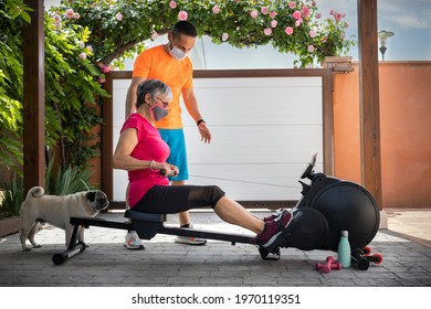 Personal trainer with protection mask and senior woman doing rowing following the teacher's instructions. Exercises at home in times of pandemic. Home gym. Family exercise