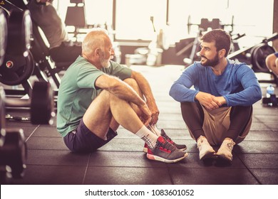 Personal trainer and senior man talking at gym after exercise.