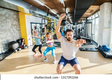 Personal trainer showing exercises with kettlebell to two sporty women. Gym interior.