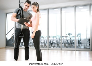 Personal trainer showing result of training plan to his female young client with suspension rope over shoulder.