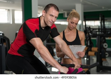 Personal Trainer Showing Young Woman How To Train On Bicycle In The Gym