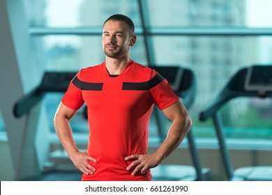 Personal Trainer Standing Strong In Fitness Centar - Gym Background With Copyspace And Flexing Muscles - Muscular Athletic Man Posing