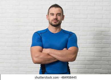 Personal Trainer Standing Strong On White Bricks Background With Copyspace And Flexing Muscles - Muscular Athletic Man Fitness Model Posing