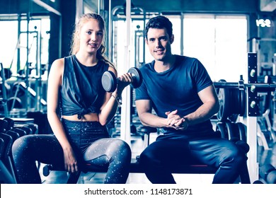 Personal trainer train beautiful sport girl in professional gym selective focus.