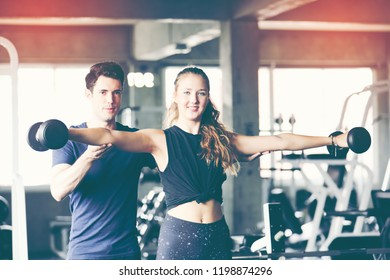 Personal trainer train beautiful sport girl with dumbbell in hand in professional gym color filter effect selective focus. Healthy lifestyle, fit and firm, sport concept.