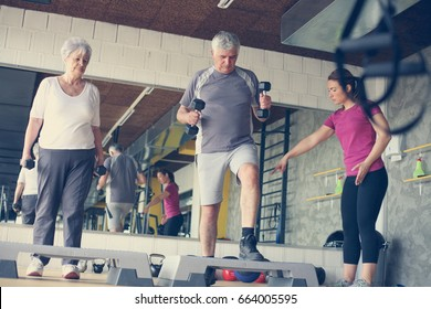 Personal trainer working exercise with senior couple. Workout in gym.