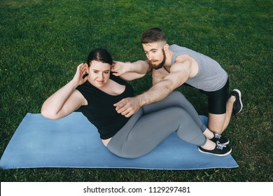 Personal trainer working with his client outdoors. Overweight woman doing situps on mat with assistance of her fitness instructor support. Sport, training, weight loss, teamwork, lifestyle concept.