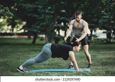 Personal trainer working with his client outdoors. Overweight woman doing pushups on mat with assistance of her fitness instructor support. Sport, training, weight loss, teamwork, lifestyle concept.