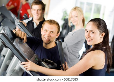 Personal trainers in the gym giving instruction and help to attractive young women