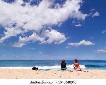 Personen sitzen am Sommer Strand