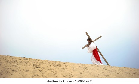 Personification of Jesus Christ carrying heavy cross in desert, crucifixion