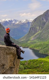 Person/man at the edge of cliff. The magnificent Bondhusdalen valley with Bondhusvatnet lake. Sundal, a hamlet on the shore of the Maurangerfjord. Folgefonna glacier, Folgefonna National Park.