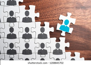 Personnel, employment and recruitment concept. Assembling jigsaw puzzle on wood desk.