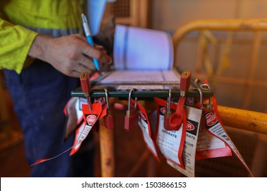 Personnel red locks attached with danger tag together with safety isolation permit lock box and defocused supervisor permit holder checking co- worker names sign on sheet at the back ground
