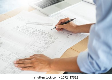 Person's engineer Hand Drawing Plan On Blue Print with architect equipment, Architects working at the table