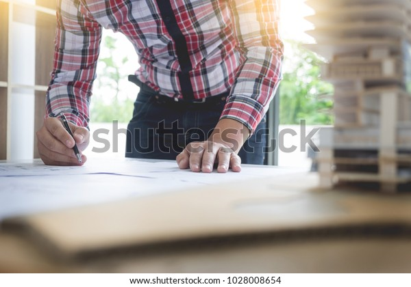 Person's engineer Hand Drawing Plan On Blue Print or working project in his office with architect equipment