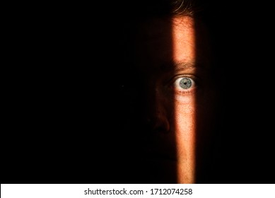 A person's face that has only partially been lit up due to looking through a crack in a doorway. The male witness could have seen many things in the other room