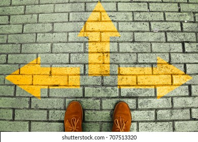 Person's feet in suede shoes is standing at tile pavement crossroad with yellow arrows print pointing in three different directions. Three ways to choose making decision which way to go. Top view