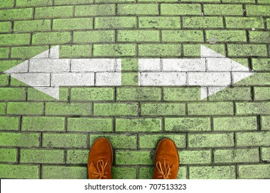 Person's feet in suede shoes is standing at tile green pavement crossroad with white arrows print pointing in two different directions. Two ways to choose making decision which way to go. Top view