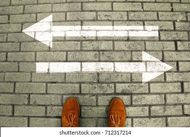 Person's feet in suede shoes is standing at tile pavement crossroad with white arrows print pointing in opposite directions. Two ways to choose making decision which way to go. Top view