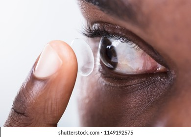 A Person's Finger Putting Contact Lens In Eye